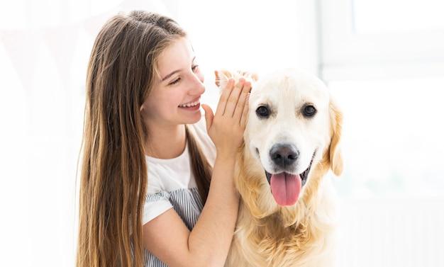 かわいい犬に秘密を告げる10代の少女の笑顔