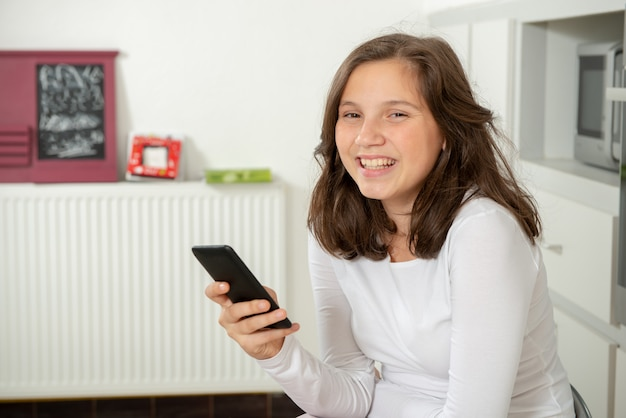Smiling teenage girl texting with smartphone at home