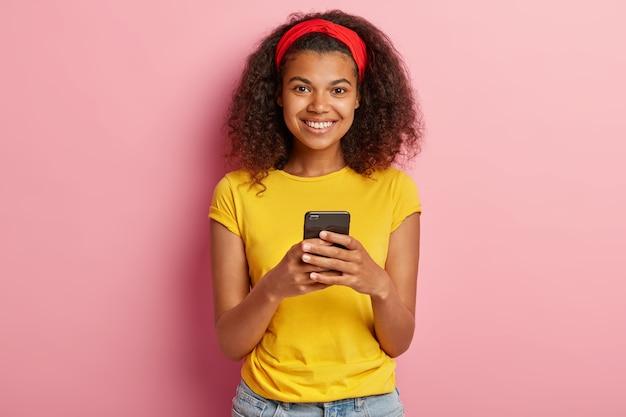 黄色のtシャツでポーズをとって巻き毛の10代の少女の笑顔