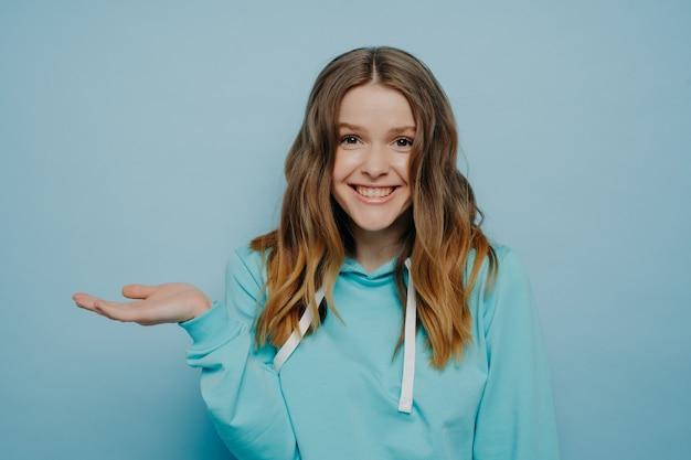밝은 파란색 배경에 서서 어깨를 으쓱하고 손을 기울이고 웃고 있는 10대 소녀, 물결 모양의 옴브레 중간 길이 머리가 눈썹을 올리는 귀여운 여성. 인간의 감정 개념