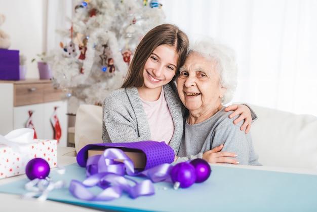 クリスマスに一緒におばあちゃんと抱き締める10代の孫娘の笑顔