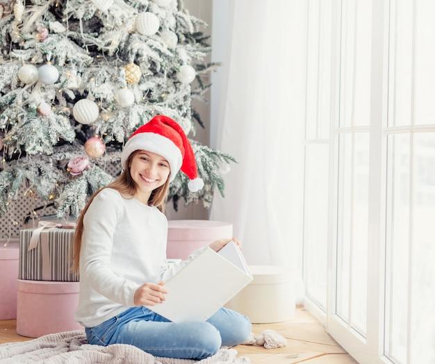 10代の帽子に座って本を保持笑みを浮かべてください。