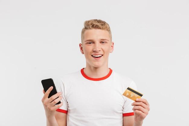 Улыбающийся подросток с чистой здоровой кожей в повседневной одежде, держащей кредитную карту и смартфон в обеих руках, изолированных на белом