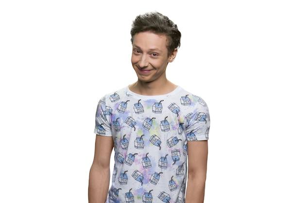 웃는 십 대 소년. 흰 벽에 고립 된 티셔츠에 즐거운 눈동자.