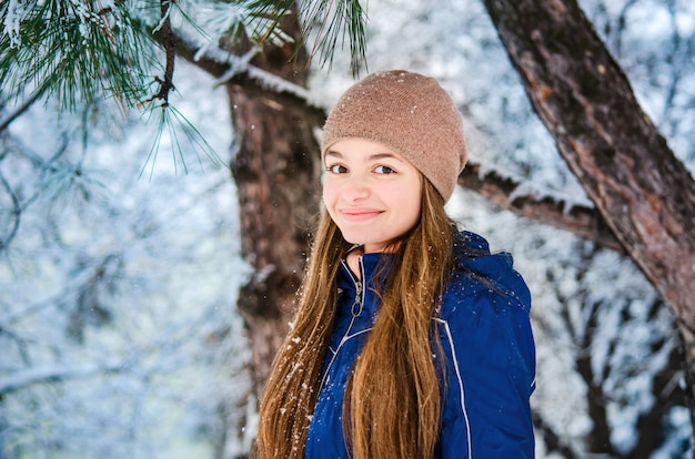 Smiling teenager girl in a blue down jacket and brown hat on a winter background of snowy fir branches