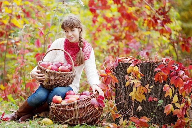 가 정원에서 사과 바구니를 들고 웃는 십 대 소녀. 가을 수확기에 과일을 먹는 유아. 아이들을 위한 야외 활동. 건강한 영양