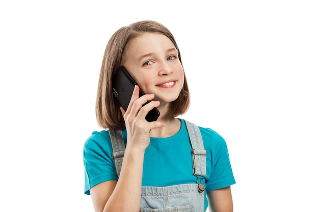 Smiling teenager girl talking on a smartphone. communication and techlogy. .