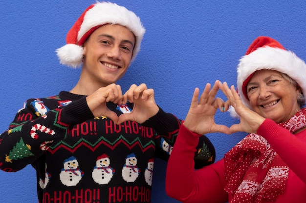 Smiling teenager grandson with grandmother wearing santa hats and christmas sweater doing heart shape with hands, family and love concept