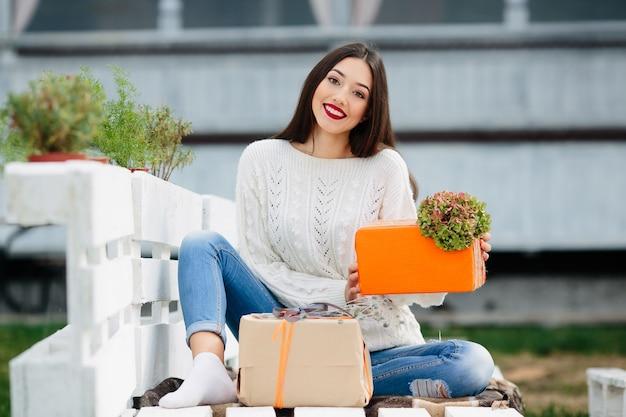 オレンジ色のギフトボックスを保持しているティーンエイジャーを笑顔