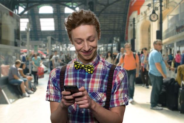 笑顔のティーンエイジャーは彼のスマートフォンでメッセージをテキストメッセージで送っています。首に蝶ネクタイをした幸せな少年。背景の混雑した場所。