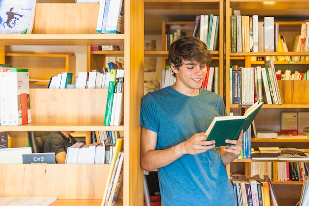 Smiling teenager leaning on bookcase and reading