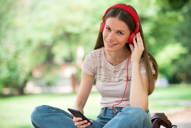 Smiling teenager listening music from phone