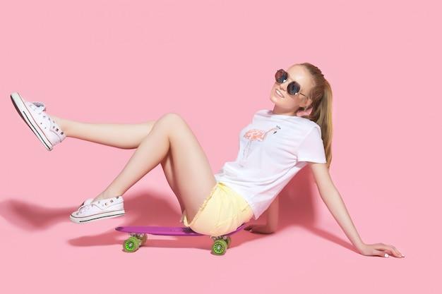 Smiling teenager sitting on skateboard