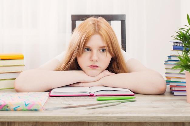 Усмехаясь девушка студента подростка делая домашнюю работу на дому, образование и концепция школы