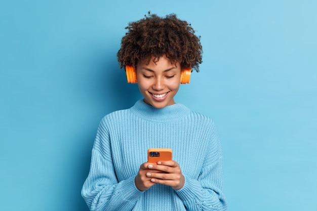 Smiling teenager with afro hair listens favorite music track holds mobile phone downloads song to her playlist dressed in casual jumper