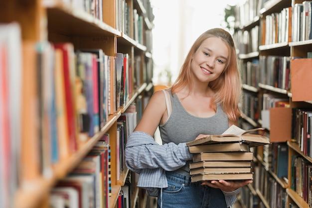 Улыбающийся подросток со старыми книгами