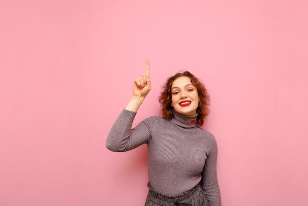 곱슬 머리와 회색 스웨터 스탠드에 웃는 십 대 여자