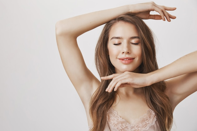Улыбающаяся нежная женщина закрывает глаза и показывает макияж на лице