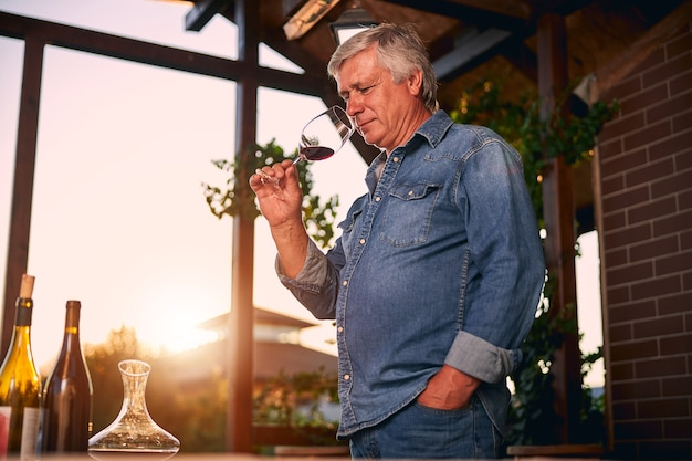 Smiling thoughtful caucasian adult standing on a sunny terrace and looking at a glass of wine in his hand