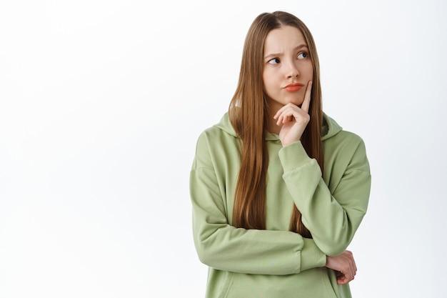 Sorridente donna premurosa che pensa, guardando da parte il logo con la faccia pensierosa, in piedi contro il muro bianco, meditando