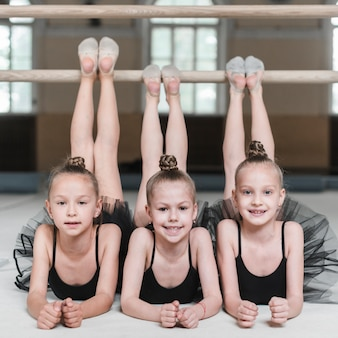 Smiling three ballerina girls stretching their legs on barre