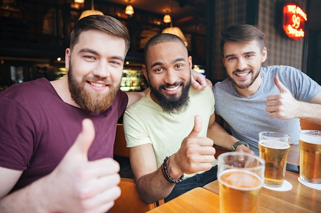 Smiling three friends sitting at the table with beer and showing thumbs up in pub