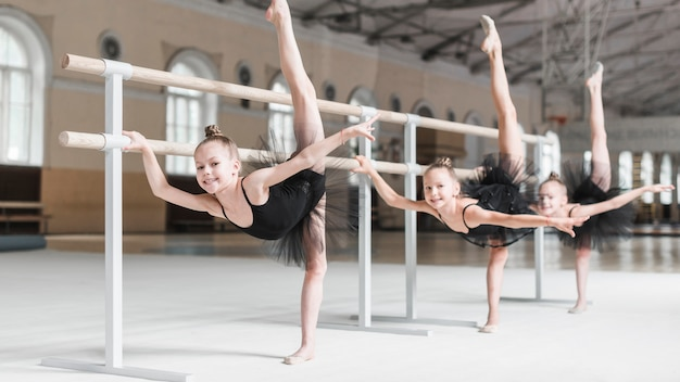 Smiling three girls with her leg up practicing in ballet class