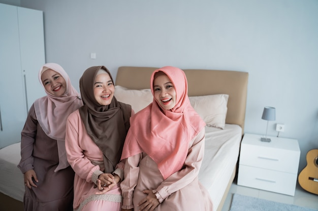 Улыбающиеся три женщины-хиджаба сидят на кровати в спальне