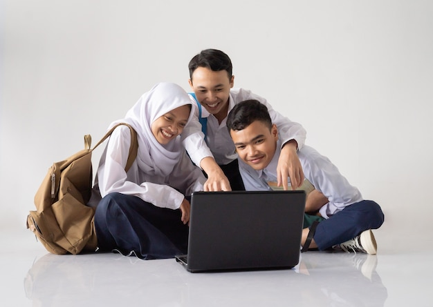 Smiling three teenagers in junior high school uniforms sitting on the floor while using a laptop tog...