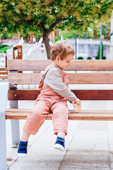 Smiling three-year-old boy catching the side of a tub sitting on a bench in the street