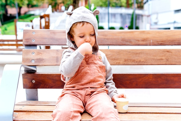 Smiling three year old boy eating ice cream in the street one autumn day