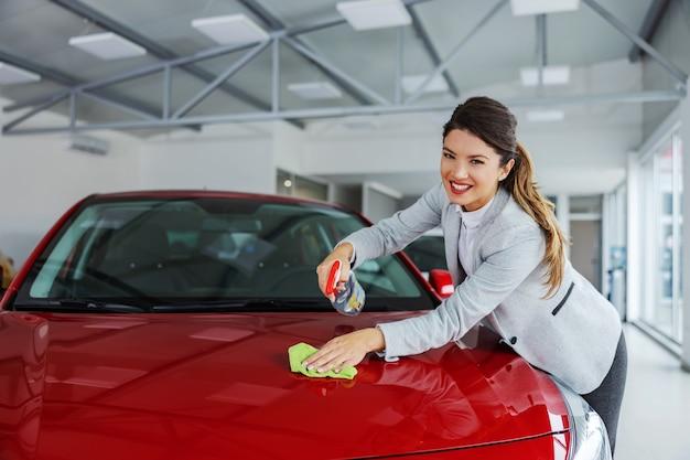 Улыбающийся аккуратный продавец женского автомобиля, протирающий автомобиль моющим средством и тканью. все должно быть блестящим и чистым.