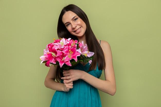 Sorridente testa inclinabile bella ragazza in felice festa della donna che tiene bouquet isolato su parete verde oliva