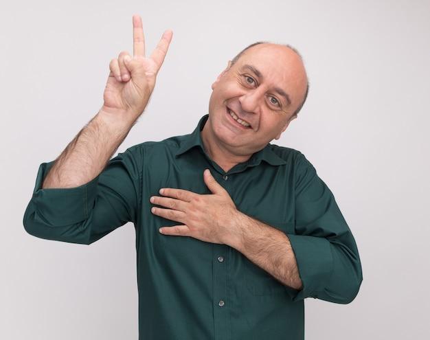 白い壁に隔離された心に手を置く平和ジェスチャーを示す緑のtシャツを着て笑顔の傾いた頭の中年男性