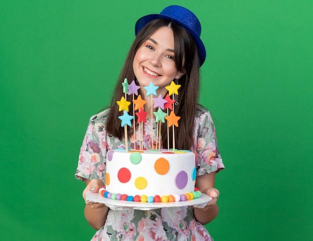 緑の壁に分離されたケーキを保持しているパーティー帽子をかぶって傾斜頭の若い美しい少女の笑顔