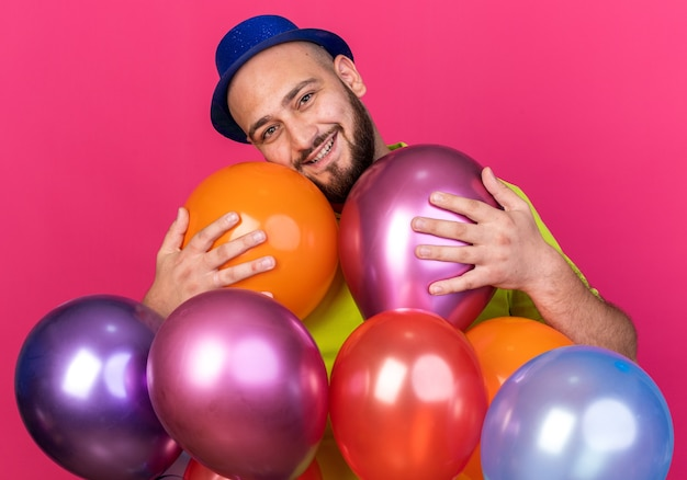 Smiling tilting head young man wearing party hat standing behind balloons isolated on pink wall
