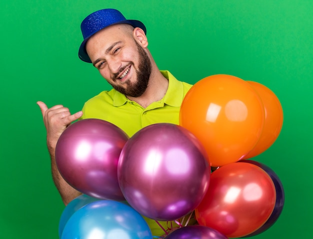 Smiling tilting head young man wearing party hat standing behind balloons showing phone call gesture isolated on green wall
