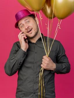 Улыбающийся, наклонив голову молодой тусовщик в розовой шляпе с воздушными шарами разговаривает по телефону, изолированном на розовом