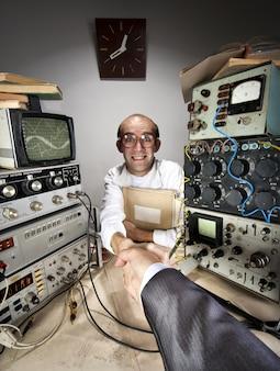 Улыбающийся робкий ученый, пожимая руку бизнесмена