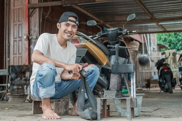 笑顔のタイヤパッチャーがバイク修理店で漏れのあるインナーチューブをこすりながら座っている