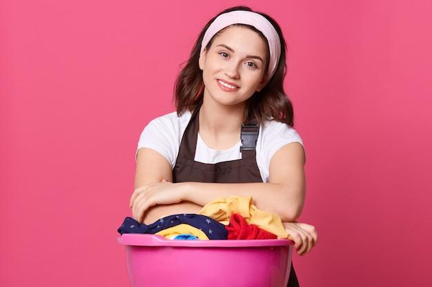 Улыбающаяся усталая красивая молодая женщина с лентой для волос и коричневым фартуком, позирует у розовой стены, смотрит в камеру с счастливым выражением лица, довольная проделанной работой.