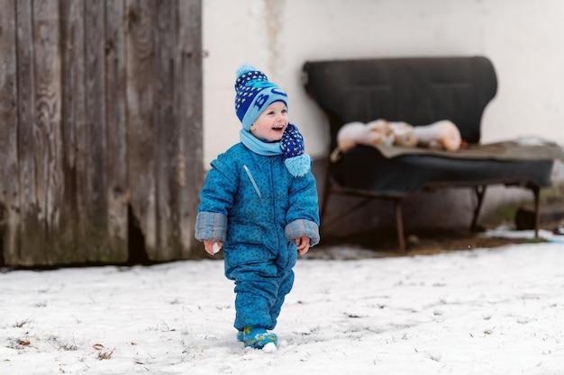 帽子とスカーフが雪の上で楽しんでいる冬の衣類の幼児を笑っています。