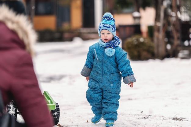 Улыбающийся малыш в зимней одежде с шляпу и шарф, наслаждаясь на снегу.