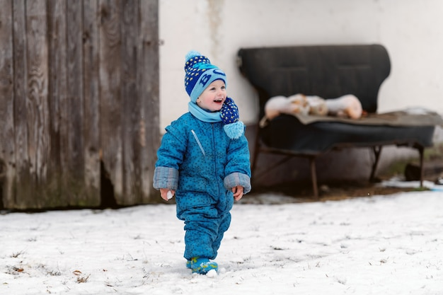 Smiling toddler in winter clothing with hat and scarf enjoying on the snow.