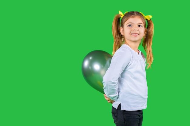 Улыбающаяся женщина-малыш с косичками прячет воздушный шар
