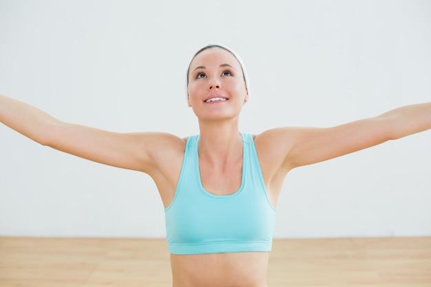 Smiling toned young woman with arms outstretched