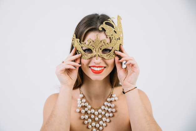 Smiling topless woman wearing golden decorative carnival mask and necklace