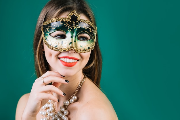 Smiling topless woman wearing masquerade carnival mask and necklace