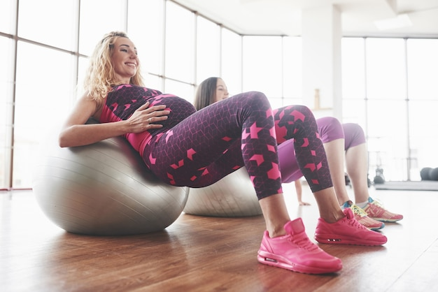 Smiling and touching the belly. side photo of two pregnant women doing fitness exersices using stability balls.