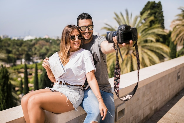 Smiling tourist couple taking self portrait through camera